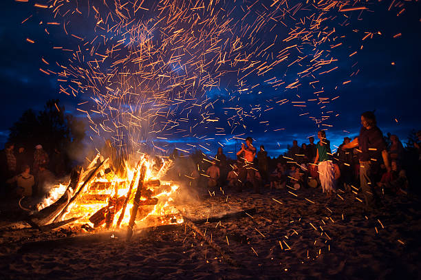 night campfire Leningrad Oblast, Russia - July 14, 2015: Big  tourist bonfire on the beach Finland Gulf during the festival. Young people dance and sing around the campfire. Deep night. bonfire stock pictures, royalty-free photos & images