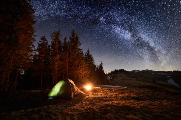 night camping. illuminated tent and campfire near forest under beautiful night sky full of stars and milky way - tent stock photos and pictures