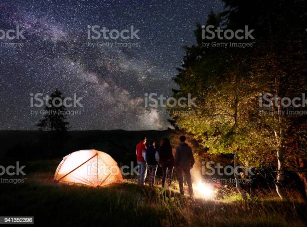 Photo of Night camping in forest under magical sky with lots of bright stars and milky way on hills background