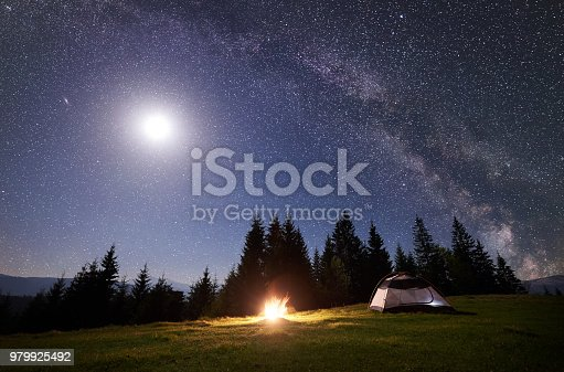 istock Night camping in mountains. Tourist tent by campfire near forest under blue starry sky, Milky way 979925492