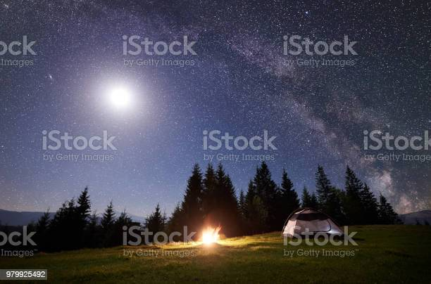Photo of Night camping in mountains. Tourist tent by campfire near forest under blue starry sky, Milky way