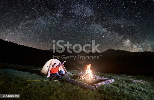 678554980istockphoto Night camping in the mountains. Couple tourists sitting in the illuminated tent near campfire, looking at beautiful night sky full of stars and milky way. Man pointing at the sky. Long exposure 700668988
