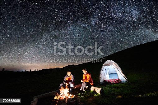 678554980istockphoto Night camping in the mountains. Man and woman tourists have a rest at a campfire near illuminated tent under incredible night sky full of stars and milky way. Low light 700668968