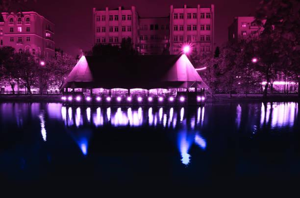 Night city cafe on river bank background stock photo