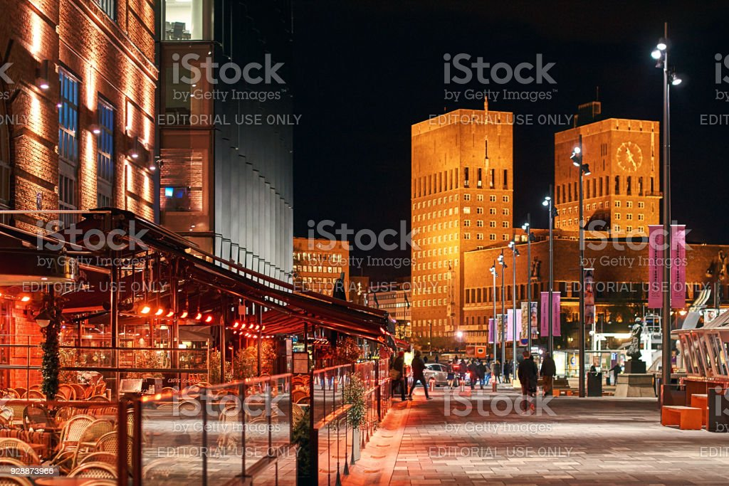 Night city view of Oslo, Norway at Aker Brygge Dock with restaurants and City Hall or Radhuset on background stock photo