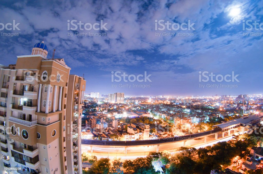 night cityscape of noida with skyscraper, monsoon clouds and moo stock photo