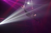 Young woman performing acrobatic element on aerial straps against dark purple background and white light