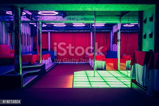 Night club interior with pole dance stage with neon lights no people
