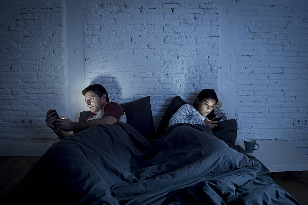 night couple in bed using mobile phone relationship communication problem – Foto