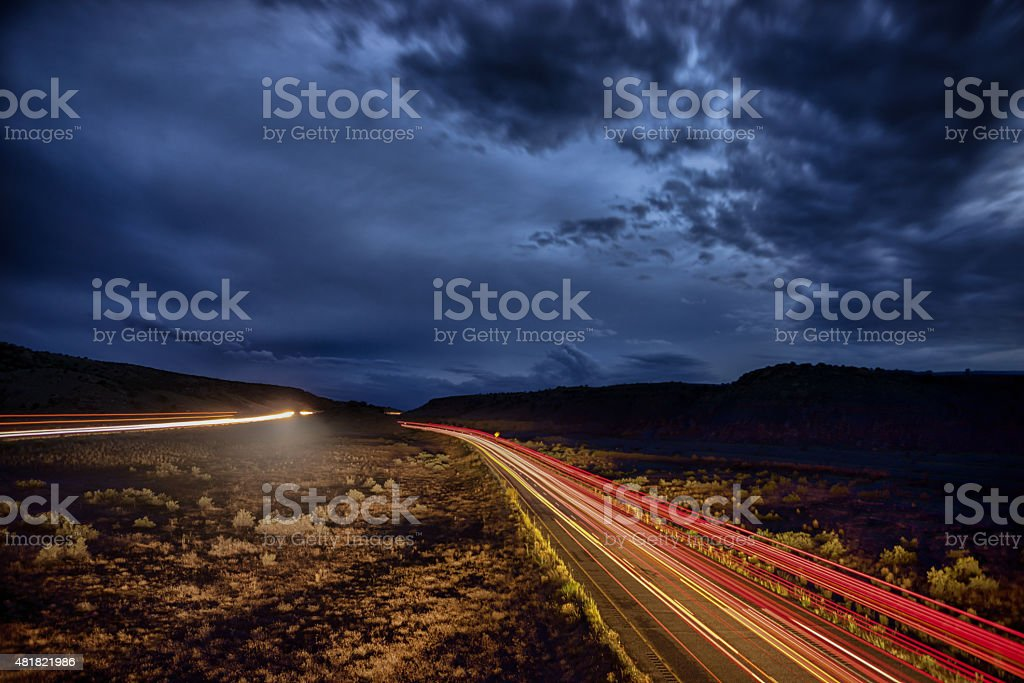 Night Desert with Storm and Light Trails from Passing Cars stock photo