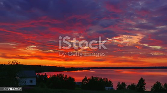 The night summer landscape - dramatic burning sky with red clouds over the lake in the countryside after sunset. Lake Tudozero, Russia.