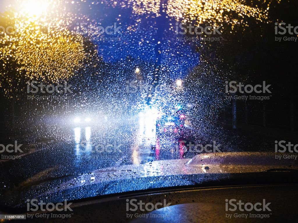 Night-time traffic on a rainswept suburban road seen through the...