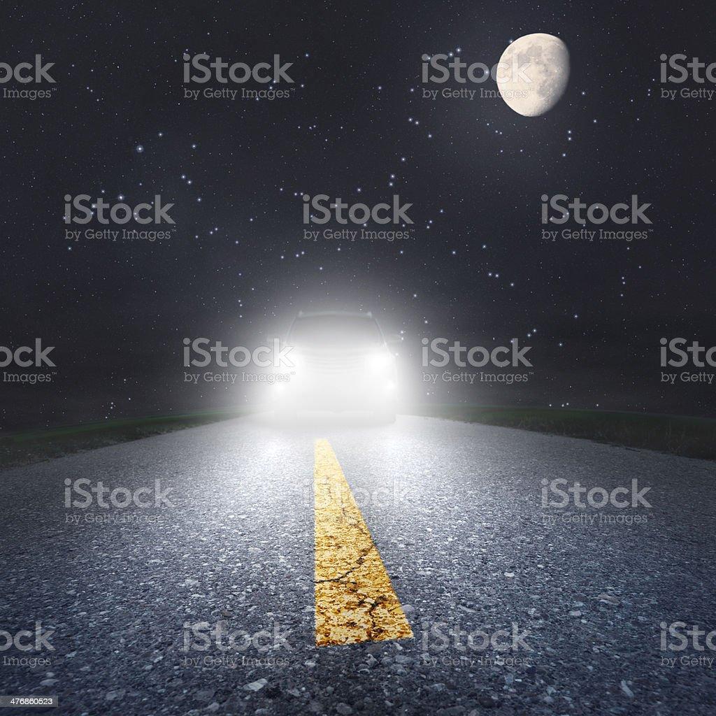 Night driving on an asphalt road towards the headlights stock photo