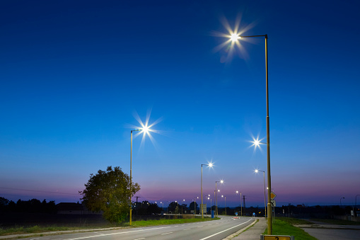 night empty road with modern LED street lights, entrance to a small town