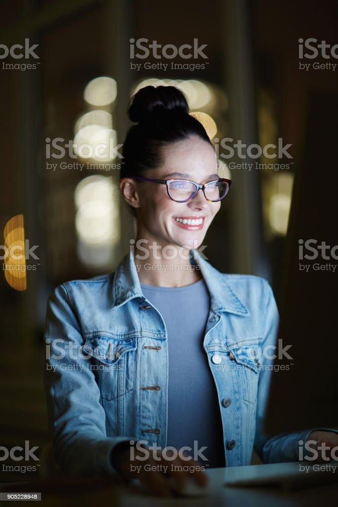 Happy girl in denim jacket siting in dark room and watching webcast...