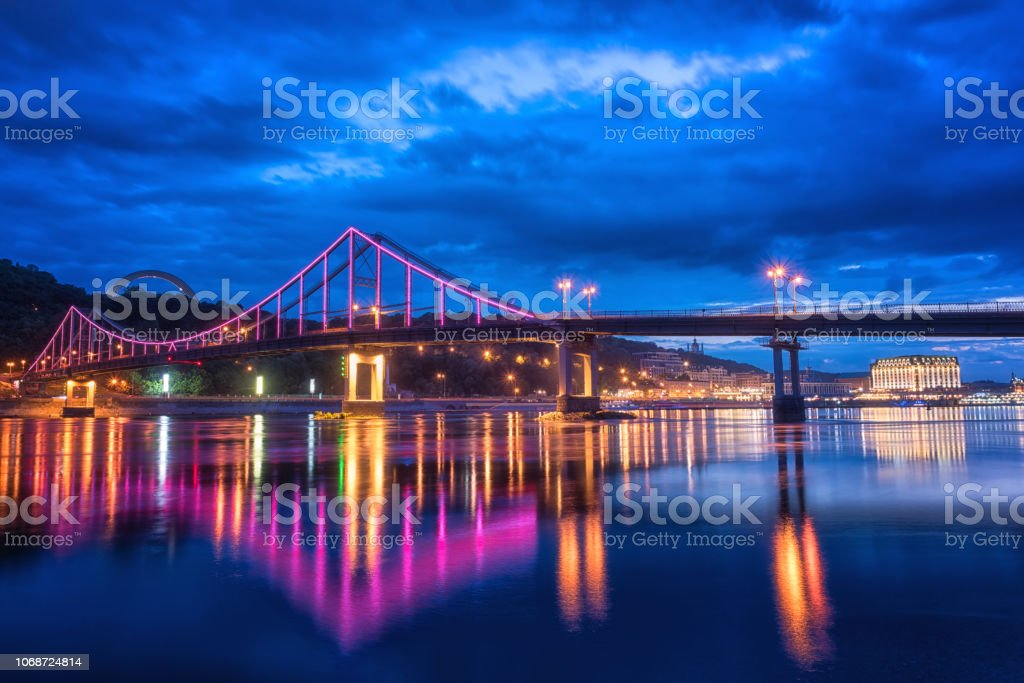 Nacht europäische Stadt in bunte Lichter und Spiegelung im Wasser, Kiew, Ukraine. Fußgängerbrücke über den Dnjepr – Foto