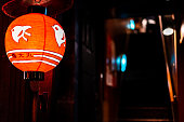 Kyoto, Japan - April 16, 2019: Night evening in Pontocho alley with traditional red paper lantern on restaurant and fish symbol dark black background