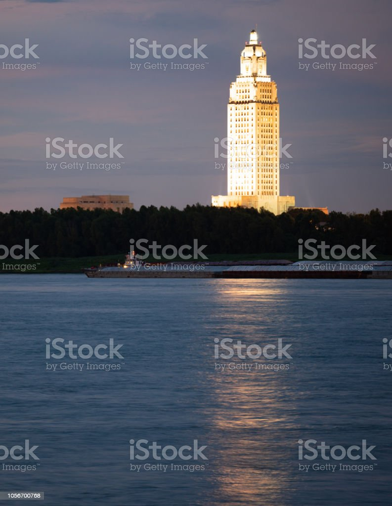 Night Falls While a Barge Travels Down Mississippi River Showing State Capital Building Baton Rouge stock photo