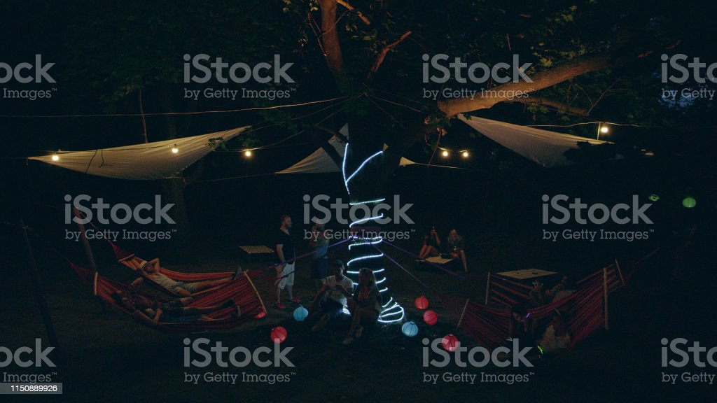 Group of people relaxing and drinking on a garden party. Illuminated...