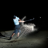 A golfer hitting out of a sand bunker at night with stars above.