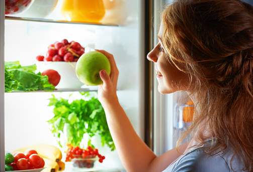 istock night hunger. Woman in the dark at open refrigerator 489989184