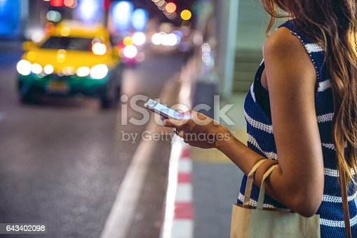 istock Night in Bangkok - Woman waiting for a taxi 643402098