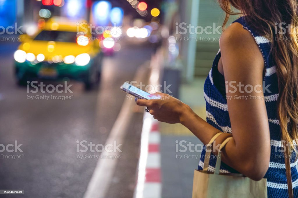 Night in Bangkok - Woman waiting for a taxi stock photo