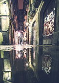 'Barcelona, Spain - December 28, 2009: Two men walking in empty old town area street of Barcelona by night. Puddle reflection.'