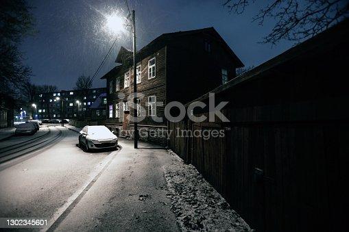 Dark street in old residential district, snowfall. Tallinn, Estonia