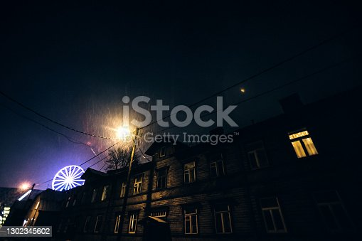 Dark street in old residential district, snowfall. Illuminated Ferris wheel in background. Tallinn, Estonia