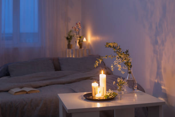 night interior of bedroom with flowers and burning candles stock photo