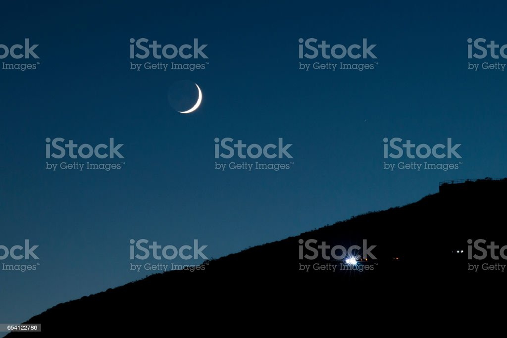 Moon is over the mountains and a car is coming up in San Francisco,...