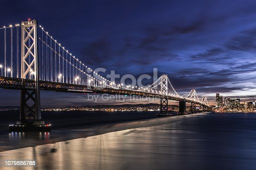 Night Landscape of Bay Bridge in San Francsico with bright lights and dark blue cloudy sky. Gray clouds, city buildings in background. Bridge lights reflecting in bay water. Cityscape