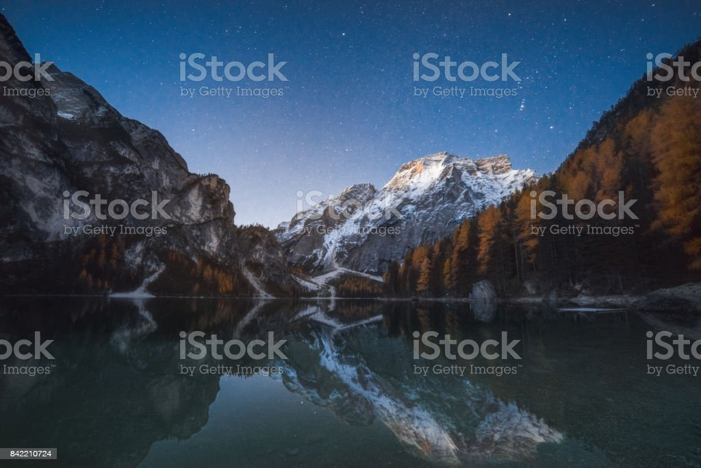 Night landscape with stars over lake and mountain, Braies, Italy stock photo