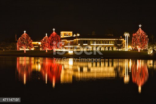 Long exposure with some blurred motion on stars on tree tops and lake surface of Christmas lights illuminate a luxury hotel in Scottsdale, AZ