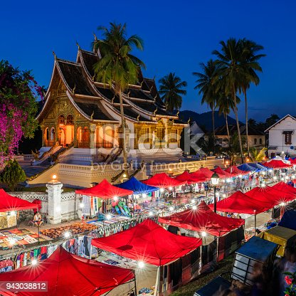 Night market in Luang Prabang is a central place for shopping local. Most product are hand made from eithic groups. The Haw Pha Bang temple on the background.