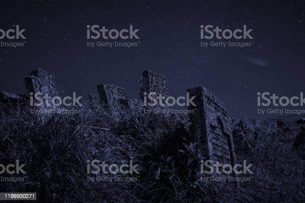 Photo of night mystery cemetery gravestones Halloween concept atmospheric scary photography with blue star sky background wallpaper pattern copy space for your text here