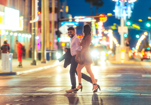 A young couple enjoying the Las Vegas nightlife together, crossing a bright street surrounded by neon.