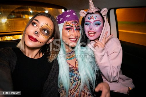 Girls riding in a taxi to the Halloween party and taking selfies.