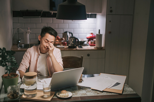 Asian chinese male working late at home dining room emotional stress with his financial bill alone at night