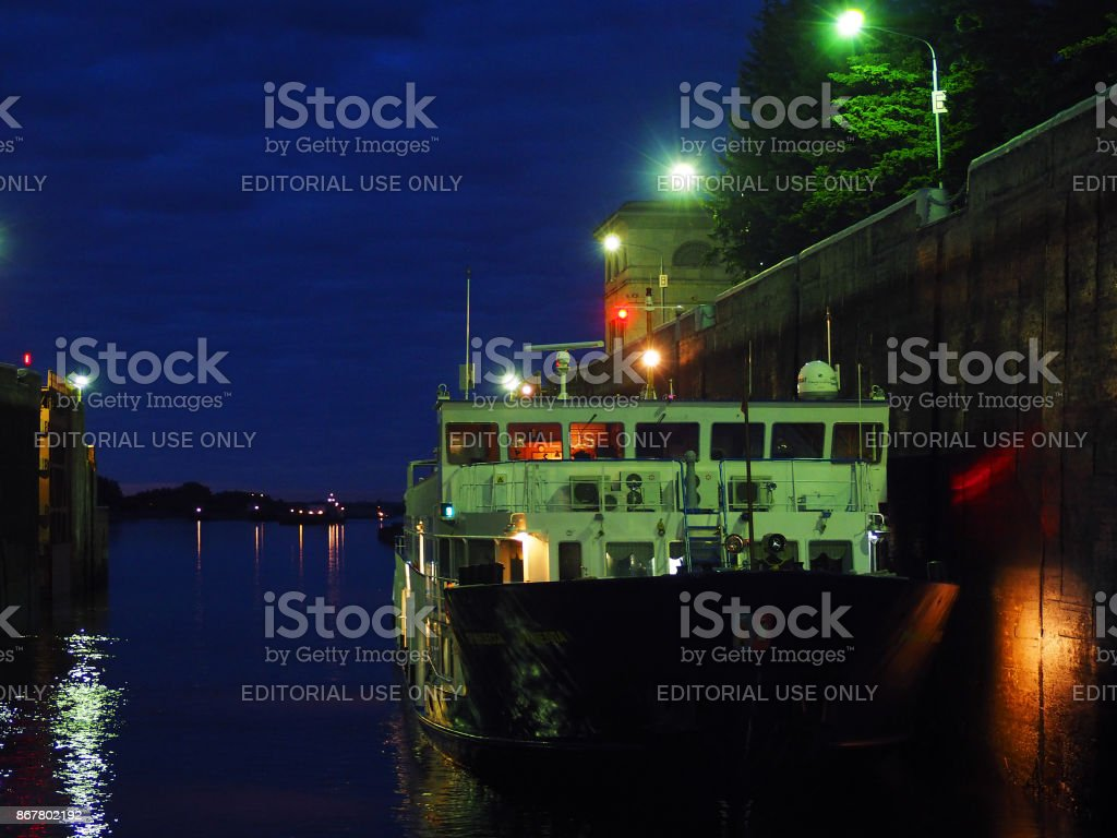 Night. Passenger ship in navigable gateway on the Moscow Canal. The rise of the vessel in the lock chamber, difference of water level, open gate stock photo