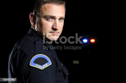 a police officer in the night with his patrol car in the background.