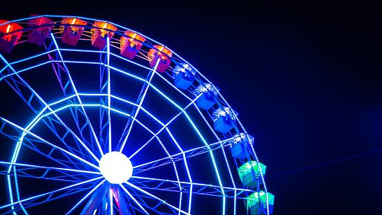 Night photo of a moving illuminated Ferris wheel in Madrid, Spain