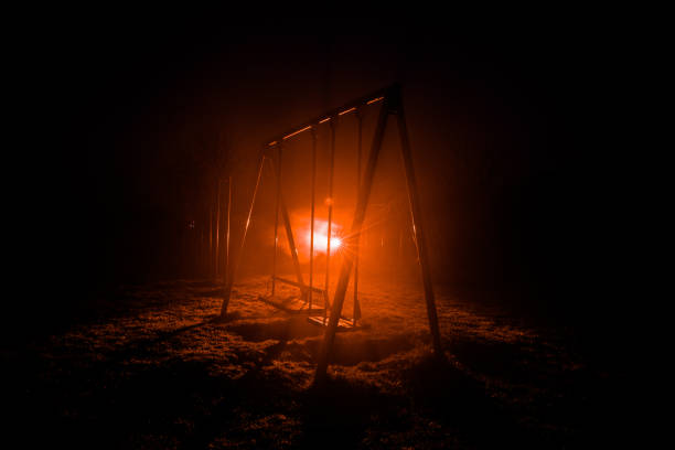 Night photo of metal swing standing outdoor at night time with fog and surreal toned light on background. Nobody there. stock photo