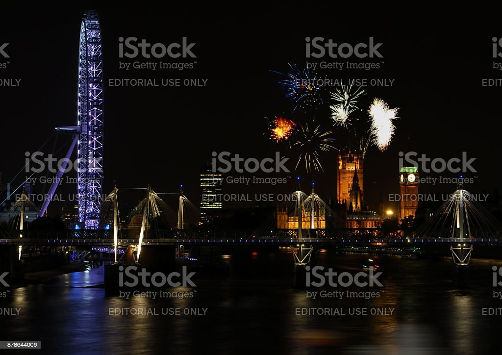 A night photo of the Millenium Eye and the Houses of Parliament with fireworks stock photo