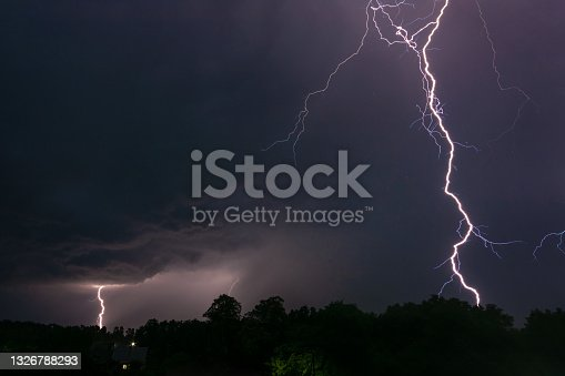 istock Night photo of two lightnings in the sky over a small village 1326788293