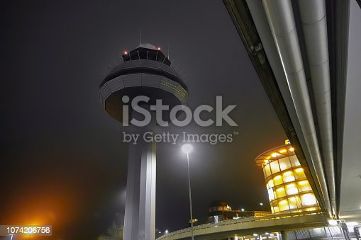 Night photograph of the tower of an airport with poor lighting and the parking garage for the passengers in the background.
