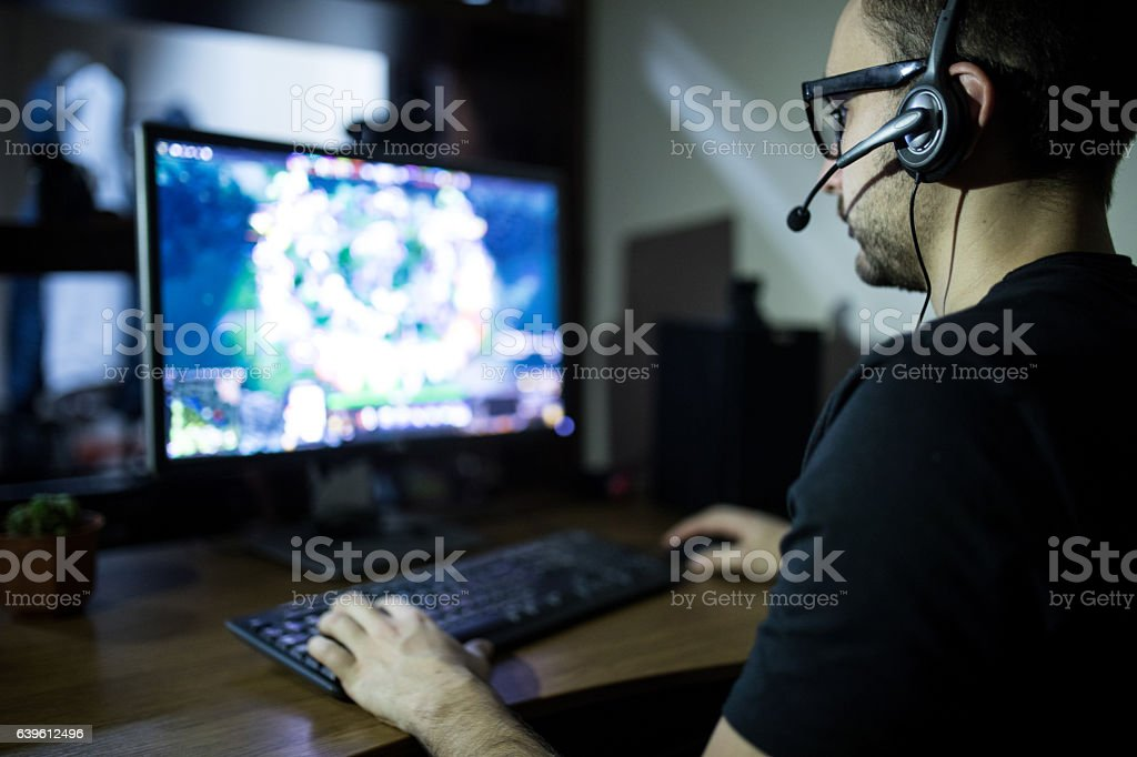 night play. young gamer in headphones and glasses using computer stock photo