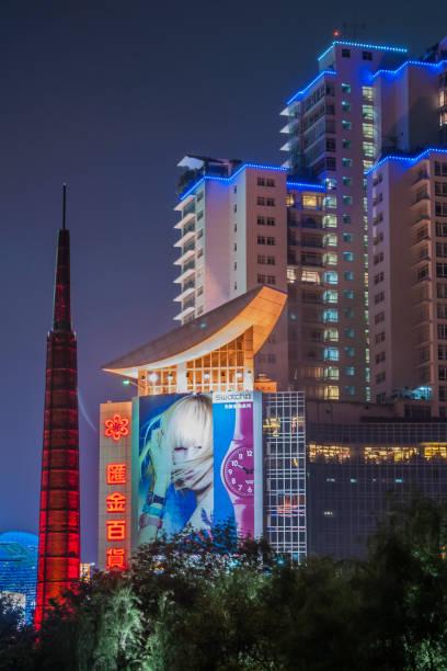 Night portrait of residential building over dark Xujiahui park, Shanghai China. stock photo