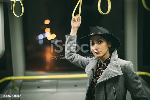 Woman holding a handle in bus and looking straight, at night